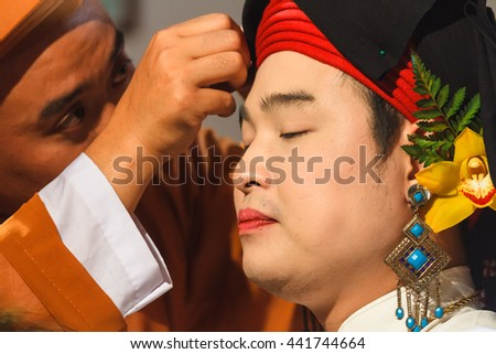 Thanh Hoa, Vietnam - October 19, 2014: A male medium is being dressed up to perform a spirit mediumship ritual in Central Vietnam. In trance the medium channels goddesses of the Dao Mau religion.