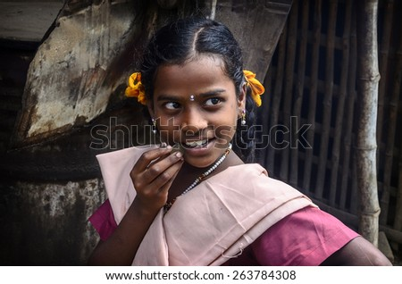 THANJAVUR, INDIA - FEBRUARY 13: An unidentified beautiful smiling schoolgirl in uniform going to home after classes at school. India, Tamil Nadu, near Thanjavur. February 13, 2013 - stock photo