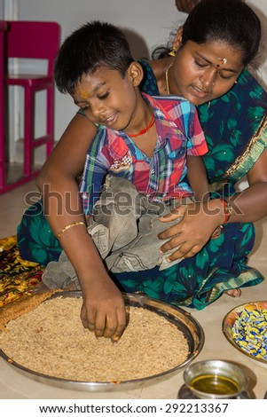 Thanjavur, India - October 14, 2013: Vijayadasam ceremony at the start of school year in Annai Fathima Primary School. Boy writes A in grain. His mother helps him.