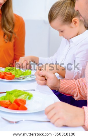 Thank god for such an abundant dinner. Pleasant friendly family holding hands together and praying while going to have dinner - stock photo