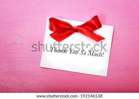 Thank you card with red ribbon on pink wooden board - stock photo