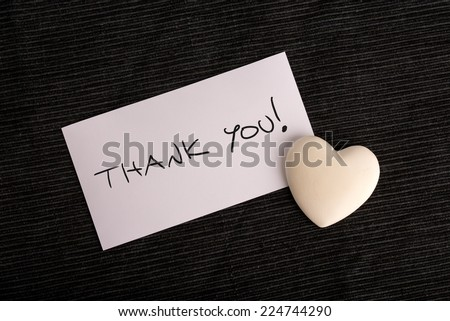 Thank you handwritten on a white card with a cream colored heart lying on a black background. - stock photo