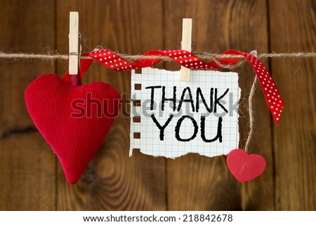 Thank You message written on a paper hanging on the clothesline on wooden background with two hearts - stock photo