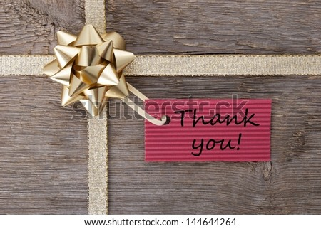 thank you on a red label on a golden gift bow as present background - stock photo