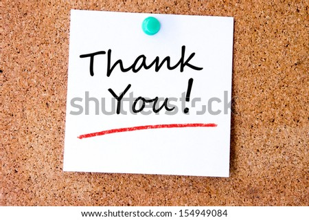 Thank You on white sticky note pinned with blue push pin on cork board - stock photo
