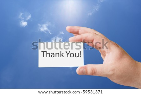 Thank you text on white paper card in hand - stock photo