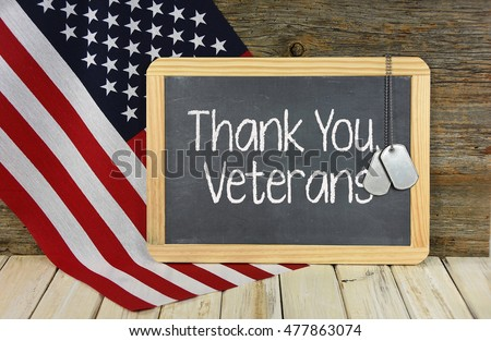 thank you to veterans with military dog tags on black chalkboard and American flag