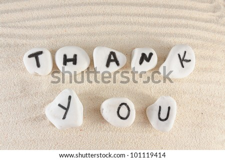 Thank you words on group of stones with sand as background - stock photo