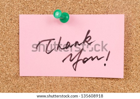 Thank you words written on paper and pinned on corkboard - stock photo