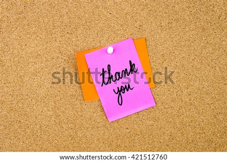 Thank You written on paper note pinned on cork board with white thumbtack, copy space available - stock photo