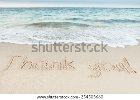 Thank you written on sand by sea at beach - stock photo