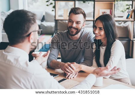 Thankful couple. Happy young loving couple bonding to each other and looking at man sitting in front of them at the desk and gesturing - stock photo