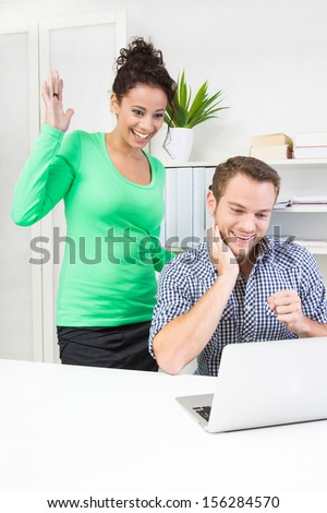 Thankful woman standing behind her colleague in office - stock photo