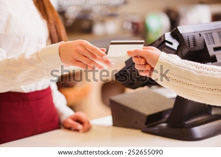 Thanks for your purchase. Cropped image of a customer paying to shop assistant by a credit card at the cash desk - stock photo