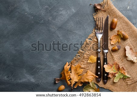 Thanksgiving autumn place setting with cutlery and arrangement of fall leaves, selective focus