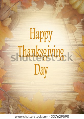 Thanksgiving border of autumn leaves, bare twigs, pinecones, wheat stalks and nuts with rustic wooden background in center. Happy Thanksgiving message included. Vintage filter applied for effect. - stock photo