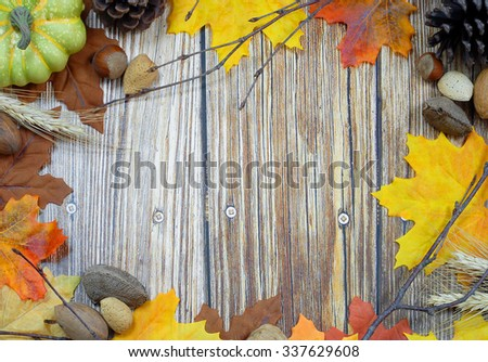 Thanksgiving border of autumn leaves, bare twigs, pinecones, wheat stalks and nuts with rustic wooden background in center. Copy space. Horizontal composition - stock photo