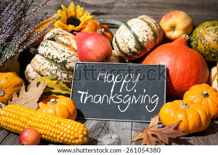 Thanksgiving day autumnal still life with pumpkins and holiday text on old wooden background - stock photo