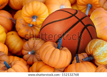 Thanksgiving Day basketball and autumn sports during harvest time with a holiday tournament ball in a pile of orange pumpkins as a concept for living a healthy lifestyle diet and exercise or fitness. - stock photo