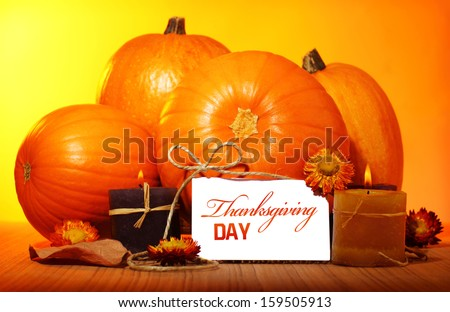 Thanksgiving day decoration for holiday celebration, pumpkin with greeting card on wooden table on yellow background, autumn season concept