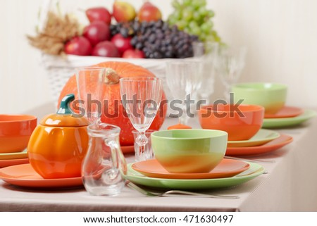Thanksgiving Day. Festive lunch with traditional table decoration - pumpkins, fruits and vegetables. Table setting in orange and green colors.