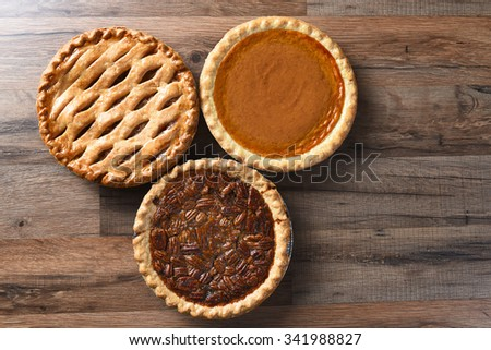 Thanksgiving desserts on a wood surface. The sweets include apple, pumpkin and pecan pies - all traditional treats for the American Holiday.