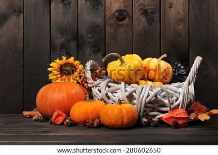 Thanksgiving - different pumpkins in rattan basket in front of old weathered wooden boards - stock photo