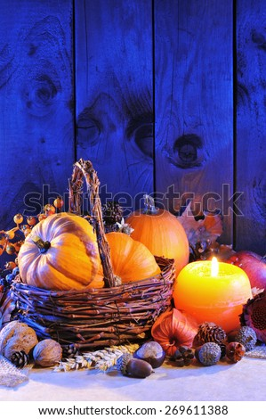 Thanksgiving - different pumpkins, nuts, maize cob and apple in rattan basket with candlelight in blue sunset light  - stock photo