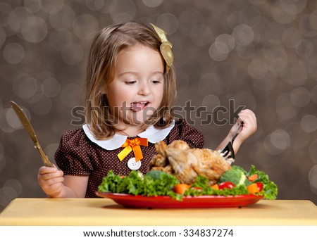 Thanksgiving Dinner.  Adorable little girl sitting at a small table with a small turkey (chicken) on a bed of greens and other vegetables.  Room for your text.