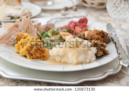 Thanksgiving Dinner Plate - Traditional holiday foods: turkey, dressing, mashed potatoes & gravy, green bean casserole, corn souffle, sweet potatoes, and cranberry salad. Shallow depth of field (DOF). - stock photo