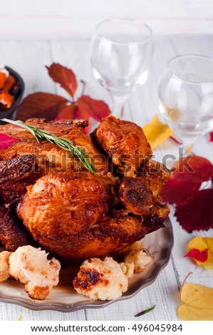 Thanksgiving Dinner. Thanksgiving table served with turkey, decorated with bright autumn leaves. Roasted turkey, table setting
