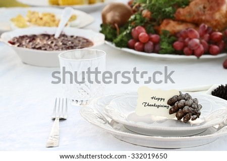 Thanksgiving Holiday table setting with cranberry sauce, deviled eggs and roast turkey in background. Happy Thanksgiving note card placed on plate. Extreme shallow depth of field. - stock photo