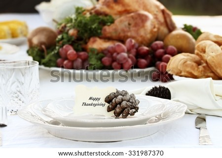 "Thanksgiving Holiday table setting with croissants and roast turkey in background. ""Happy Thanksgiving"" note card placed on plate. Extreme shallow depth of field with selective focus on card."