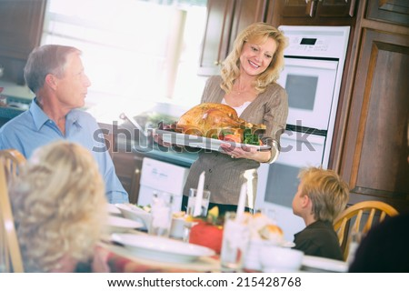 Thanksgiving: Mother Brings Holiday Roast Turkey To Table - stock photo