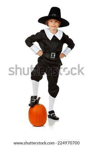 Thanksgiving: Pilgrim Boy Standing With Foot On Pumpkin - stock photo