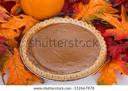 Thanksgiving pumpkin pie with colorful autumn leaves - stock photo
