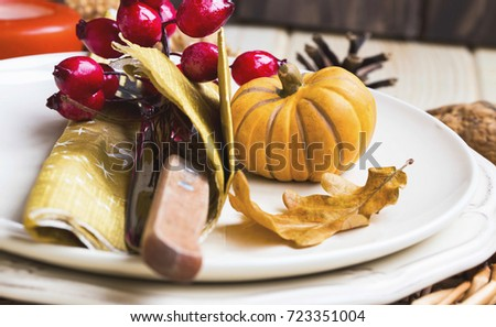 Thanksgiving setting table decoration with cutlery, plates and autumn decorations
