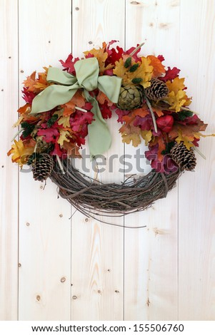 Thanksgiving wreath for Fall season greeting hanging on wooden wall - stock photo