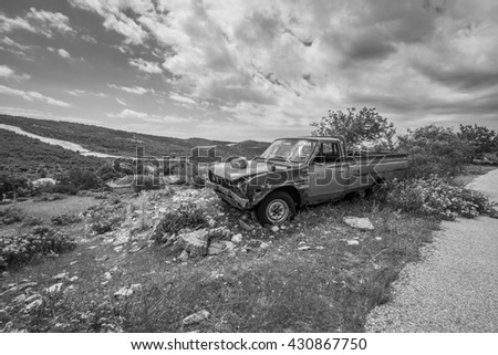 THASSOS, GREECE - MAY 17 2016: An abandoned rusty truck over looking the picturesque town of Theologos, a popular sightseeing destination for holiday makers on the sleepy Island of Thassos, May 2016. - stock photo