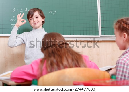 That is OK. Little smiling boy standing near green blackboard in classroom and showing that everything is OK