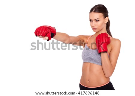 That is real  boxing. Concentrated sporty woman in sportwear and boxing gloves boxing while standing isolated on white background - stock photo