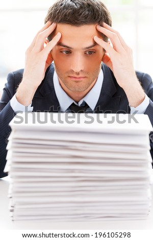 That is too much. Depressed young man in shirt and tie looking at the stack of paperwork and holding head in hands while sitting at his working place - stock photo