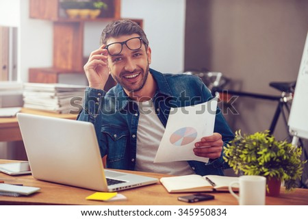 That was a great month! Handsome young man holding paper with colorful diagram and looking at camera with smile while sitting at his working place in office - stock photo