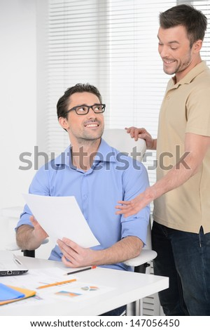 That was easy! Two happy business people looking at the business documents and smiling - stock photo