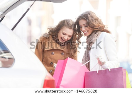 That was really good shopping. Two beautiful young women showing what did they get to each other - stock photo