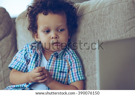 That was unexpected! Little African baby boy looking at his laptop and looking confused while sitting on the couch at home  - stock photo