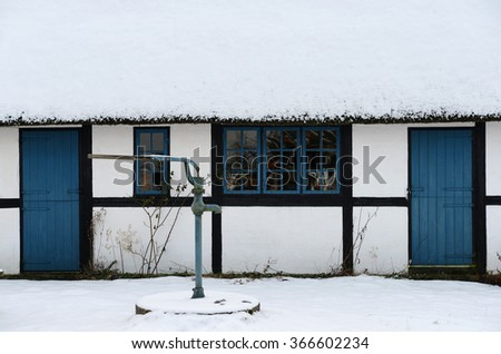 Thatched house with blue windows and doors in a rural area in denmark.  Covered in snow.