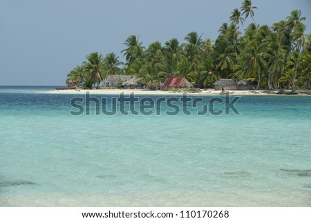 Thatched houses and palm tree forest in island, San Blas islands, Caribbean, Panama, Central America. - stock photo