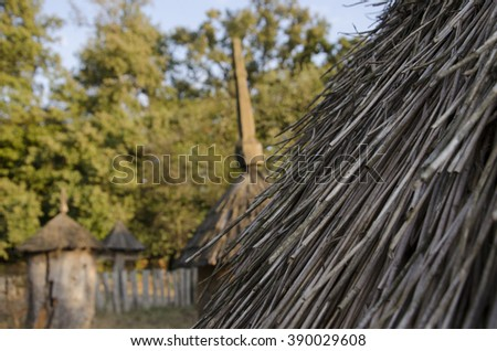 thatched roof huts. View of the old retro beehives through straw roof made of sticks - stock photo
