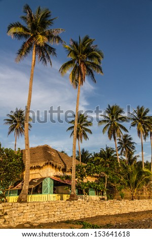 Thatched roof restaurant on a tropical beach in a sunset - Donsol, Philippines - stock photo